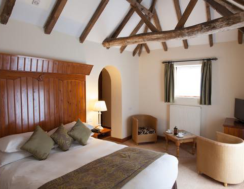 Courtyard Room - Image shows a luxurious bed, cathedral ceilings with rustic beams, and a small sitting area