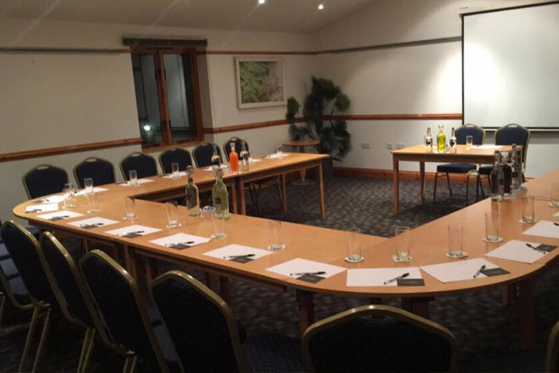 Long, U-shaped table in one of our spacious functions rooms