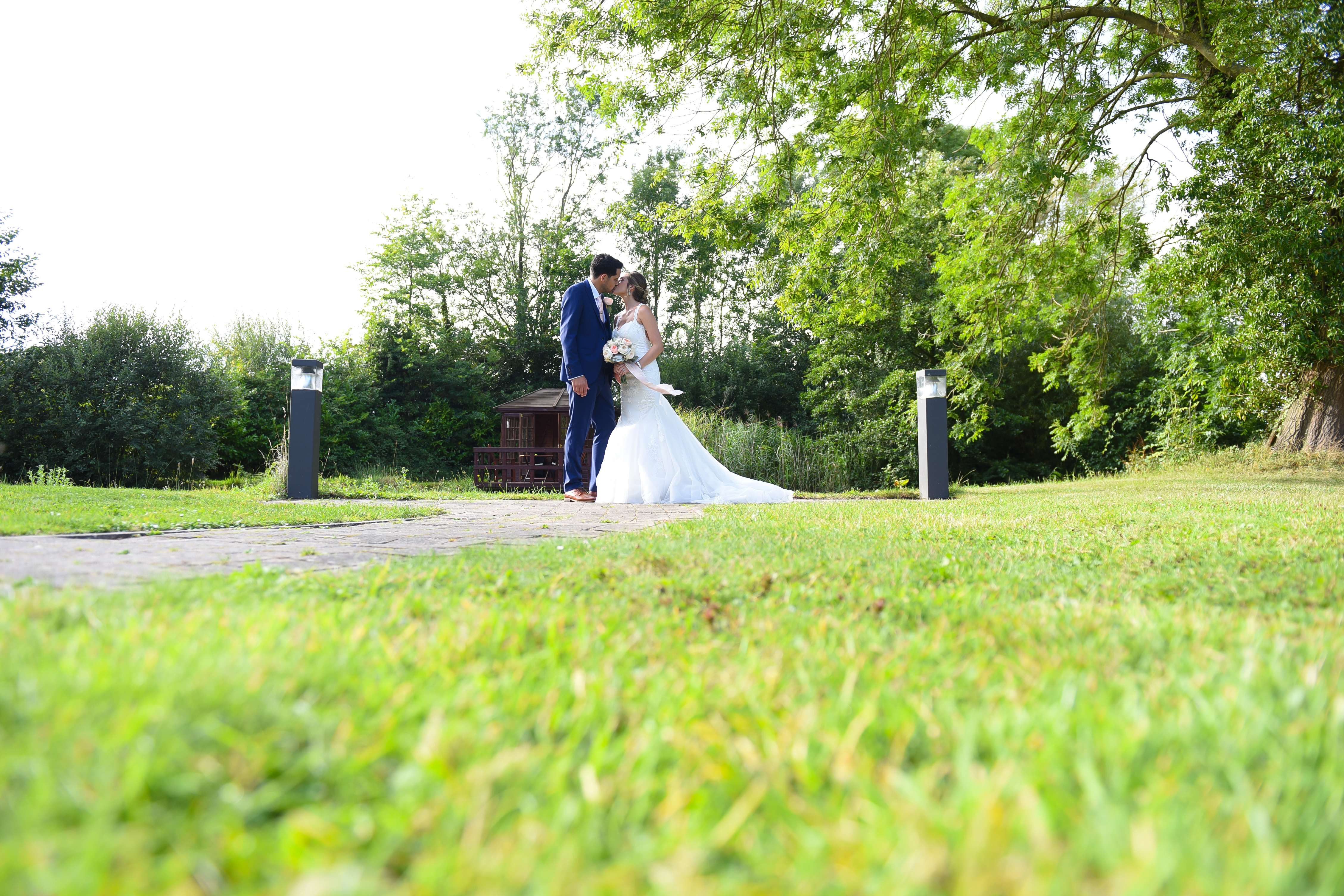 Bride and Groom Kissing in Field at Ivy House Country Hotel
