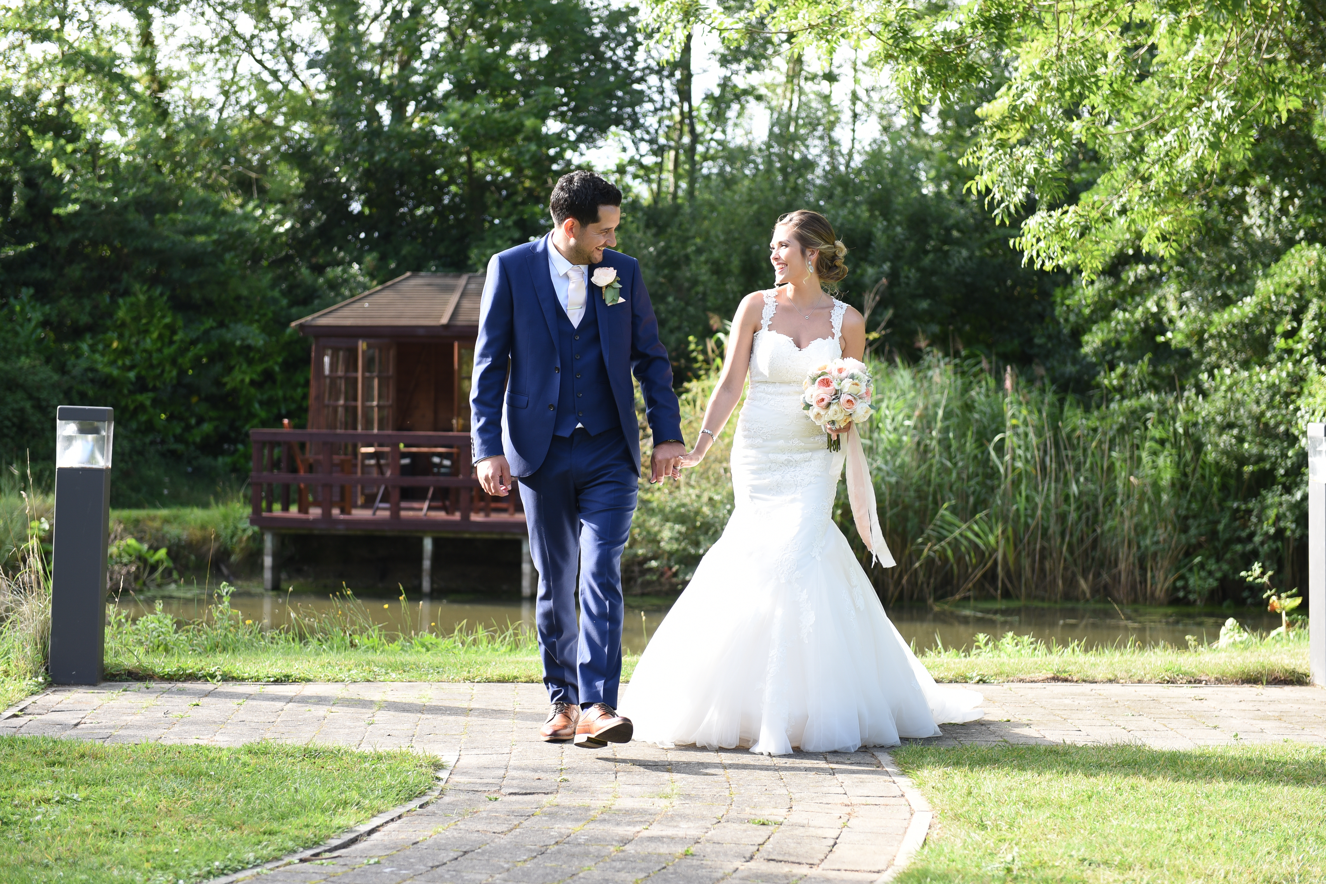 Newlyweds Holding Hands Walking Near Lake at Ivy House Country Hotel