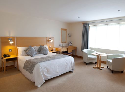 Executive Room - Image shows a spacious room with a luxurious bed, desk, and sitting area
