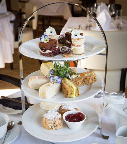 A scrumptious high tea featuring scones, sandwiches, and mini cakes