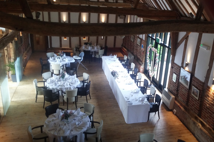 Overhead view of event venue set up with tables, chairs, and decor in rustic space