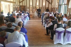 Wedding ceremony - Guests, bride, and groom seated in white seats with purple ribbons