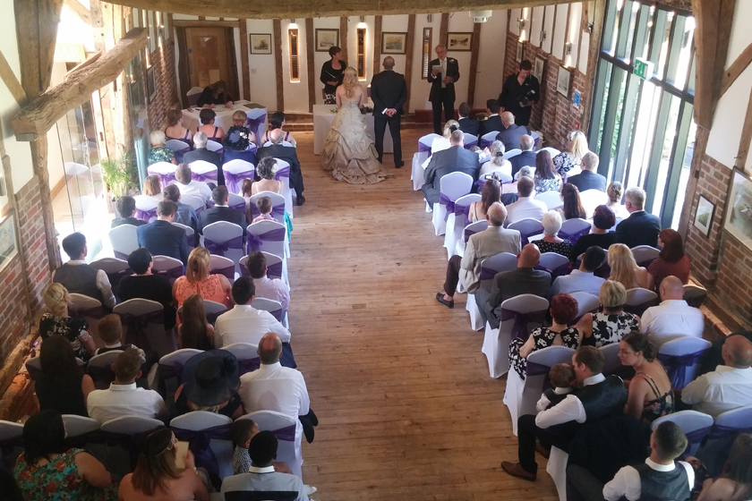 Wedding ceremony in Lowestoft with white chairs decorated with purple ribbons