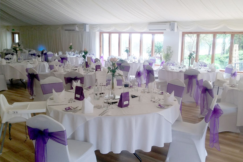 Crisp white tables and chairs decorated with purple ribbons for a wedding