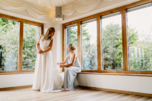Bridesmaid Helping Bride With Her Dress at Ivy House Country Hotel