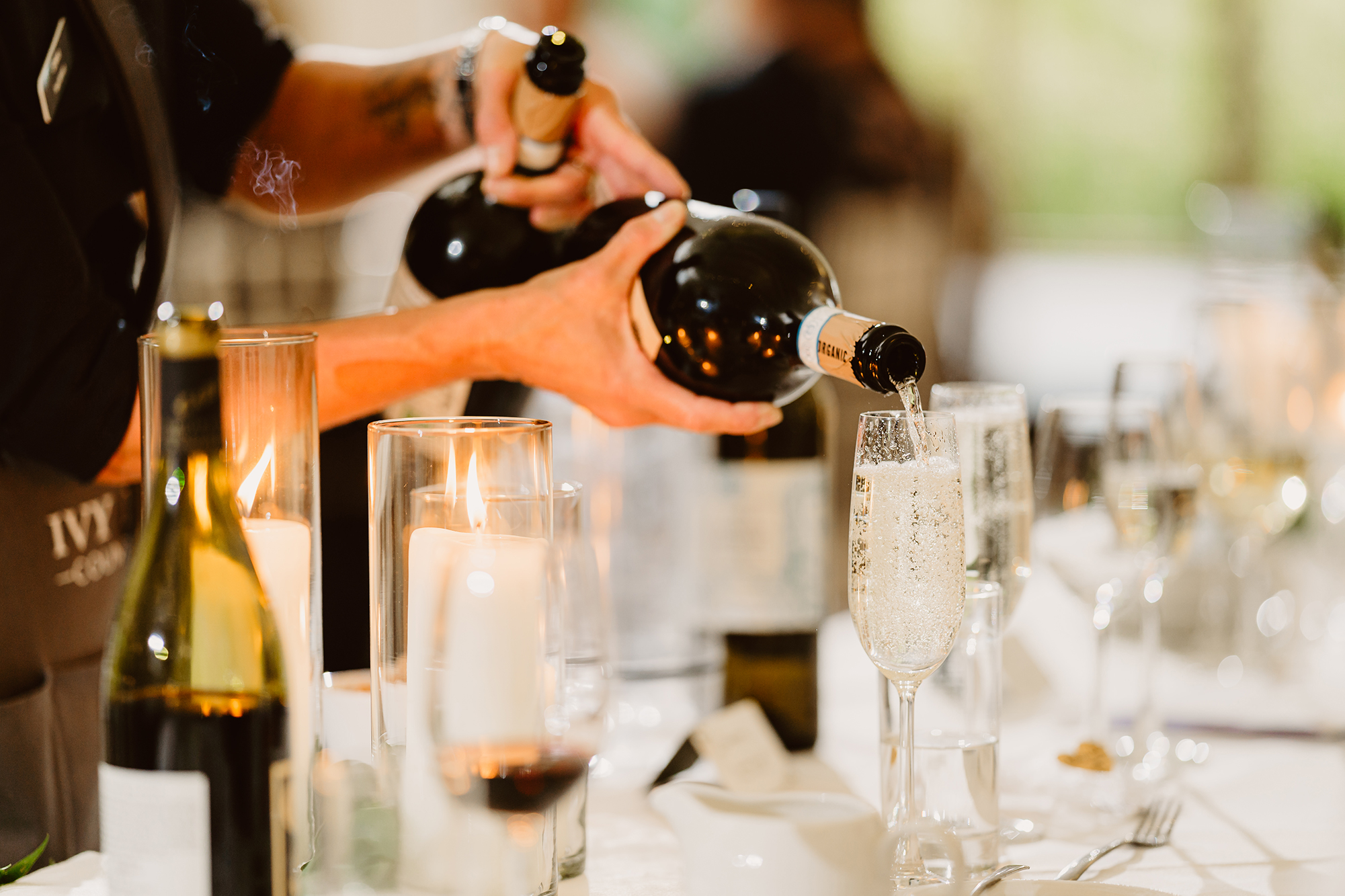 Server Pouring Champagne For Guests at Ivy House Country Hotel Wedding