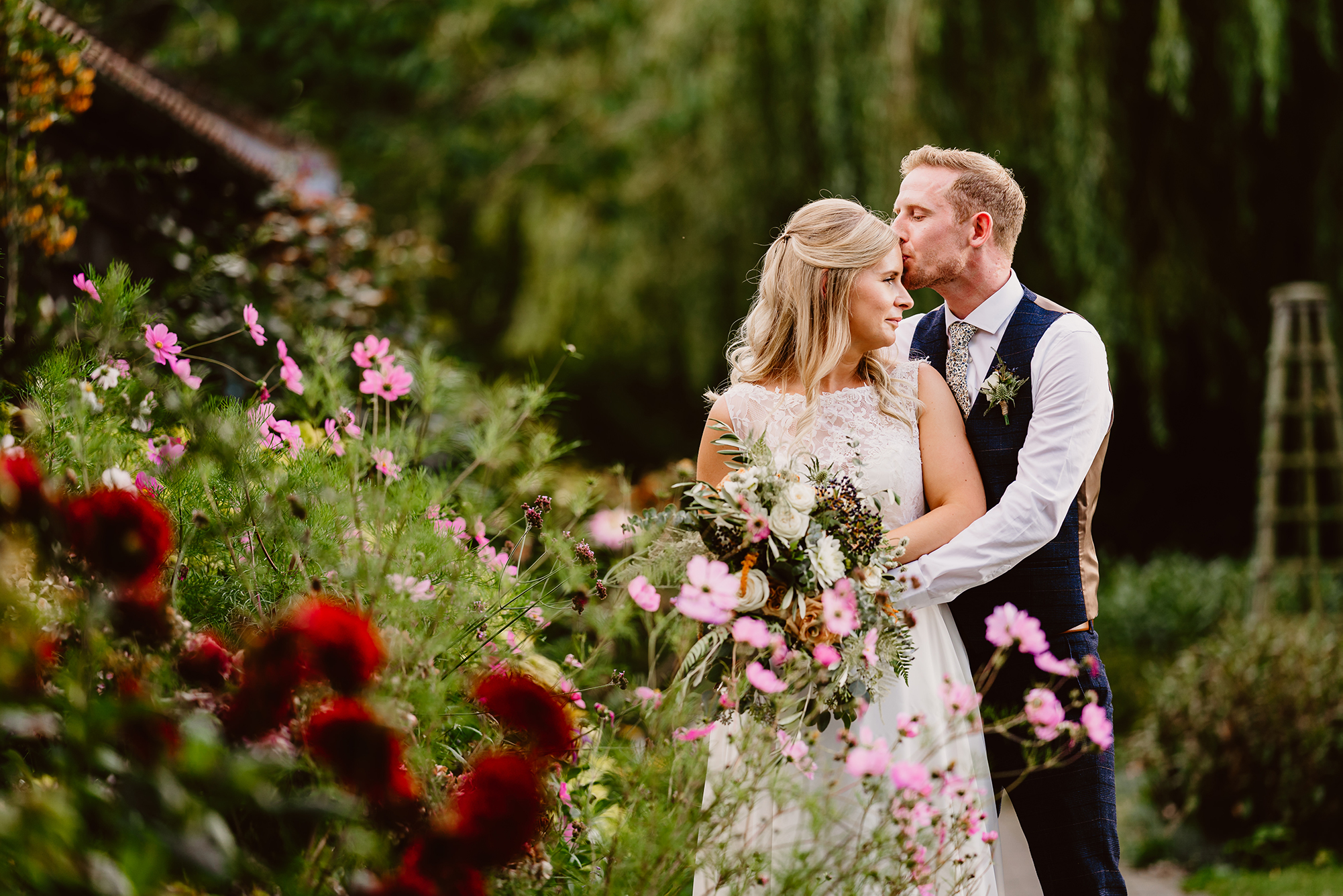 Newlyweds Genevieve & John Share Kiss in the Flower Gardens at Ivy House Country Hotel