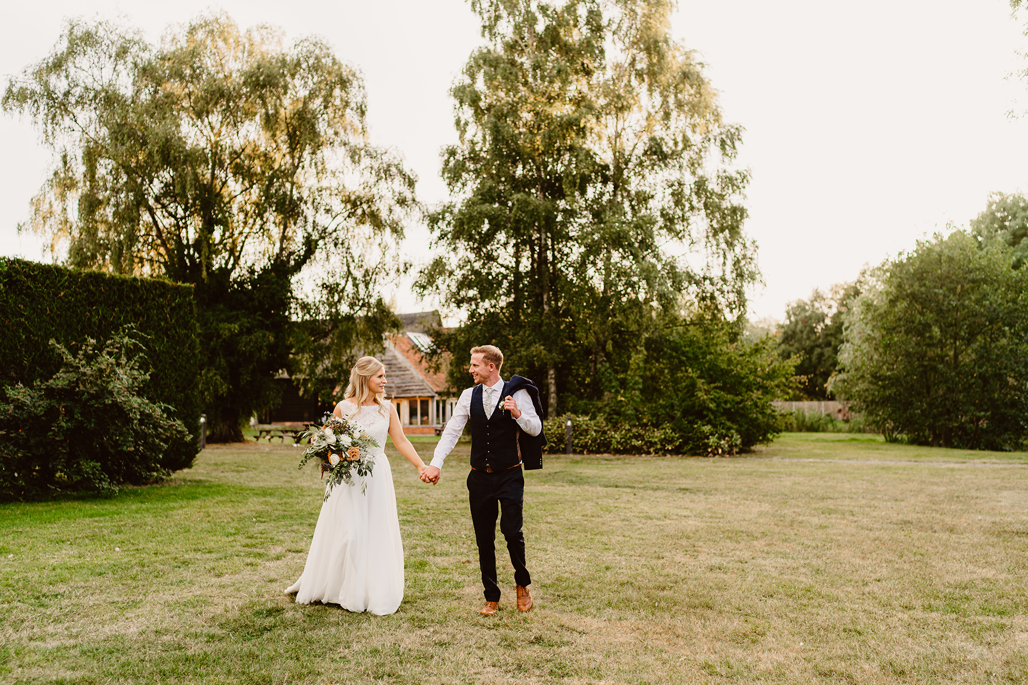 Newlyweds Genevieve & John Hold Hands Outside at Ivy House Country Hotel