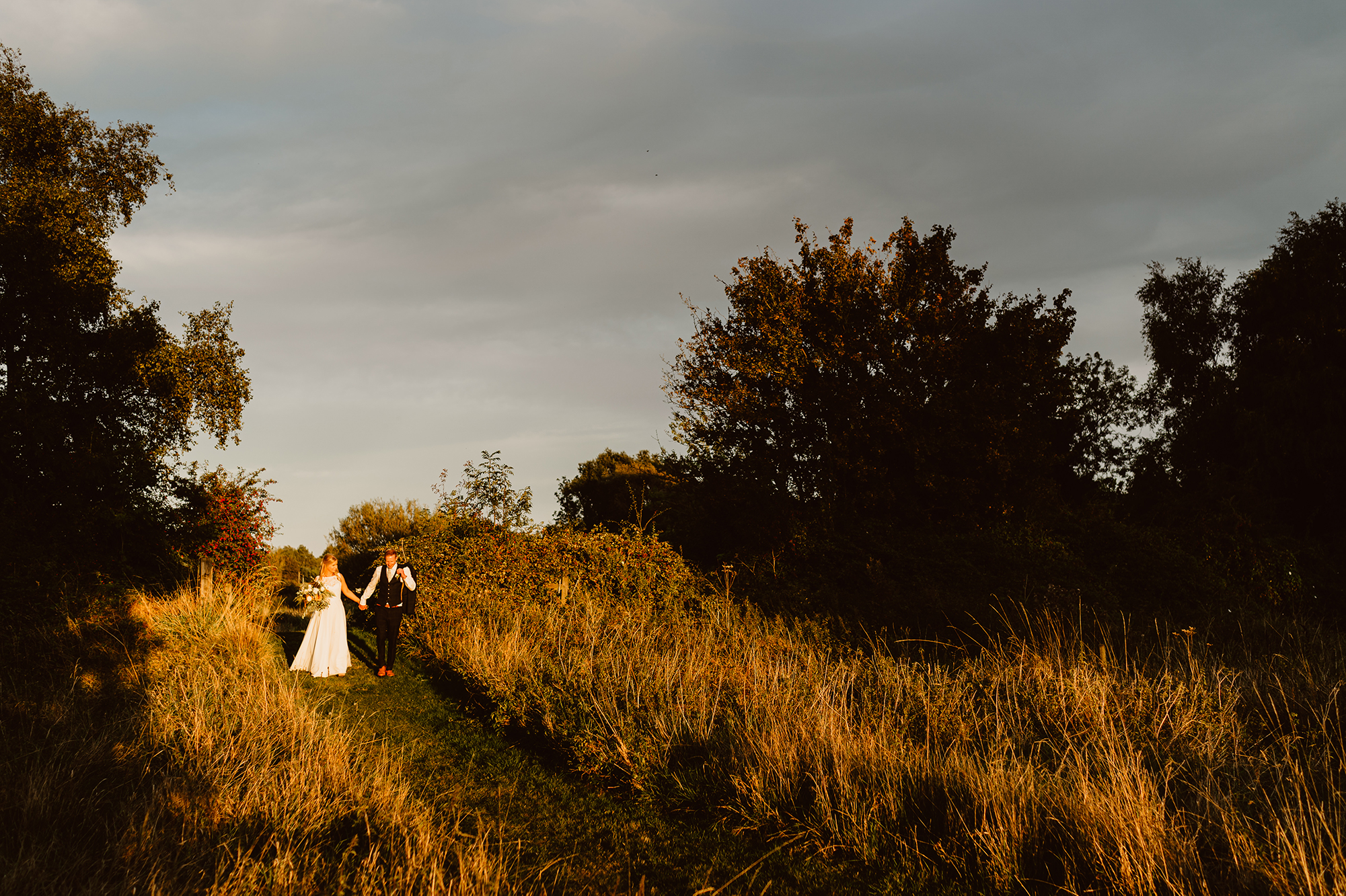 Bride and Groom Genevieve & John Walking Hand in Hand at Sunset at Ivy House Country Hotel