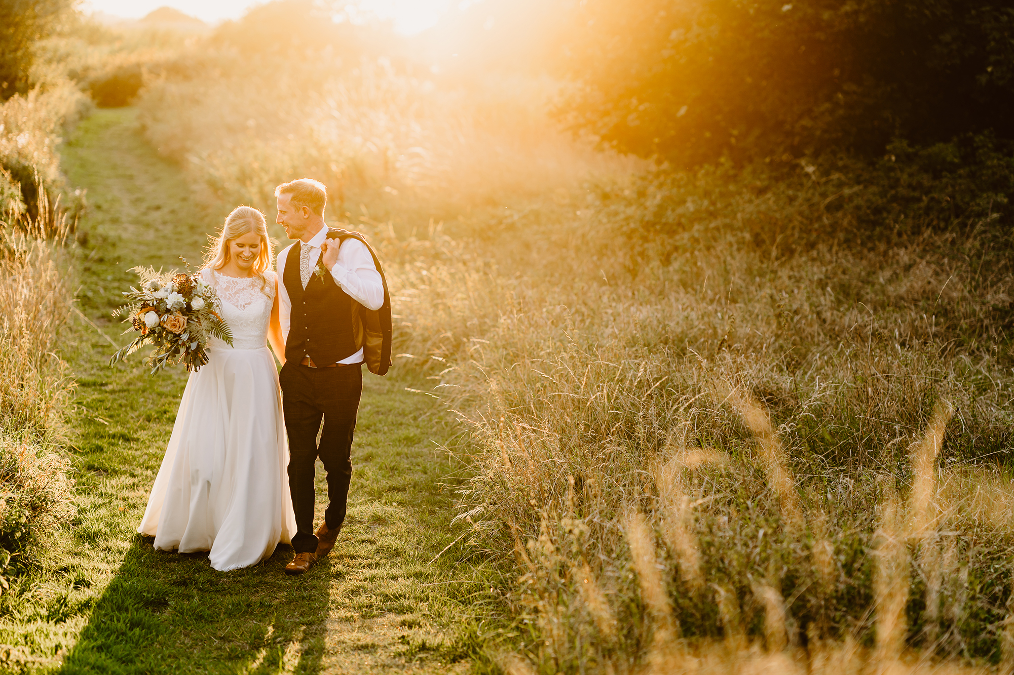 Bride and Groom Holding Hands with Bouquet of Flowers at Sunset