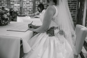 Couple signing marriage register in black and white