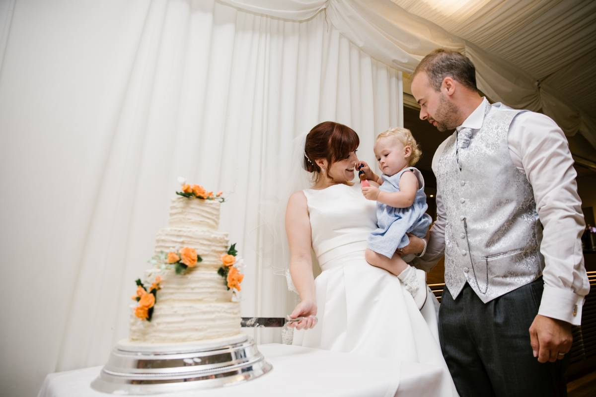 Bride cutting wedding cake with husband and baby