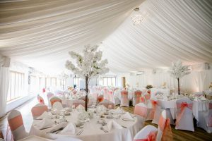 Ivy Hall set for Olly and Louise's wedding reception with chair covers and cherry trees
